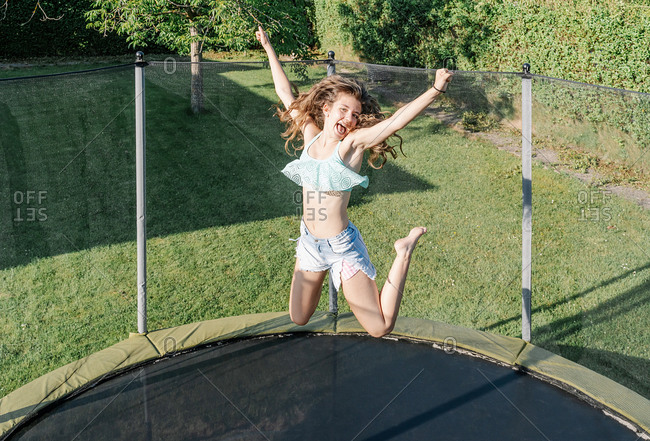 Horizontal photo of a smiling young brunette teenager jumping on a trampoline with net around on the green yard outdoors. The girl wears short jeans and a top and looks fun, active