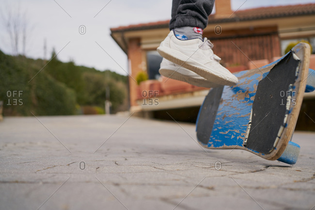 Crop kid in sneakers riding shabby skateboard on asphalt path