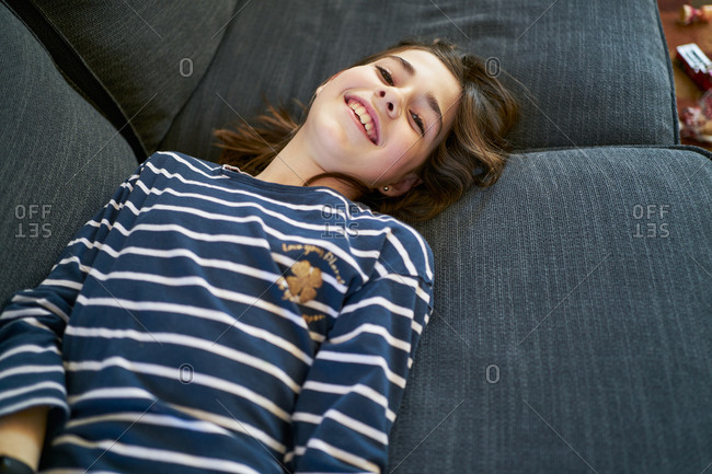 From above girl smiling while resting on soft couch at home