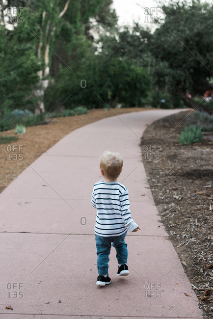 One year old boy walking along a path in Balboa park in San Diego