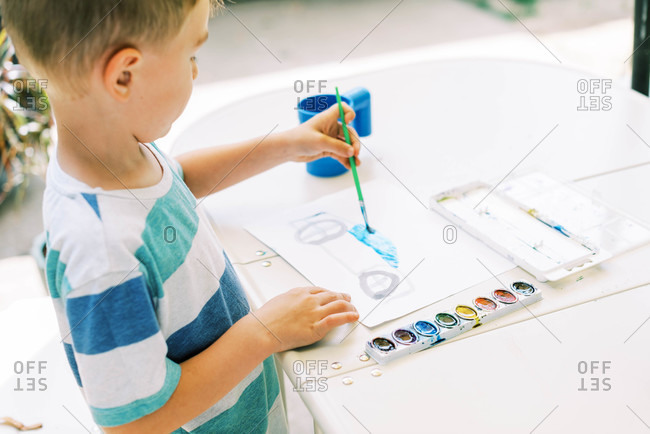 Little boy painting a car with watercolors outside on the patio