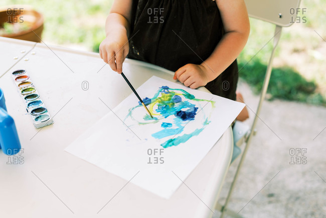 Little toddler girl painting with watercolors outside on the patio