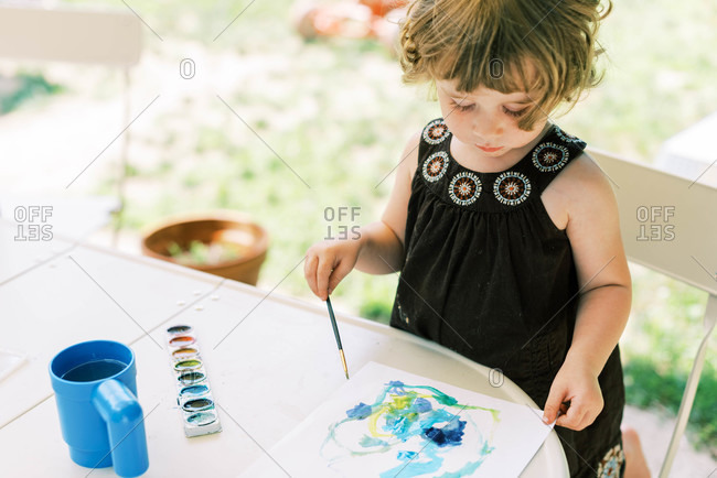 Toddler girl painting with watercolors outside on the patio