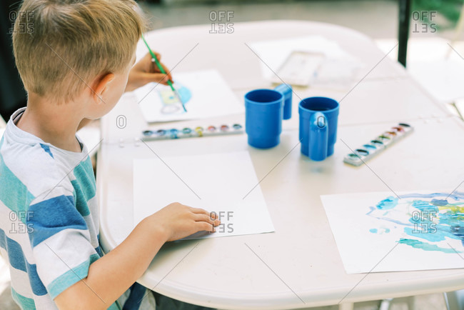 Little boy painting with watercolors outside on the patio