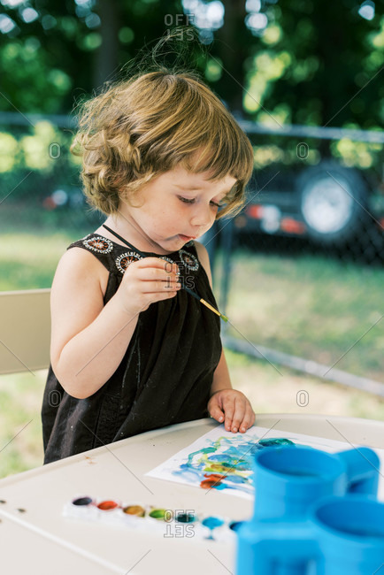 Little artist painting with watercolors outside on the patio