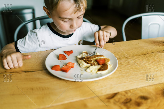 Little boy eating a pancake with fresh strawberries at home