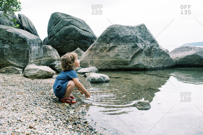 A toddler girl holding a stick at a rocky beach