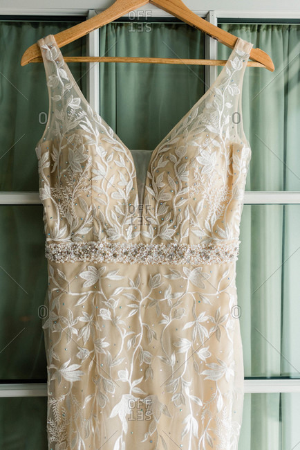 Close up of a wedding dress hanging on a door