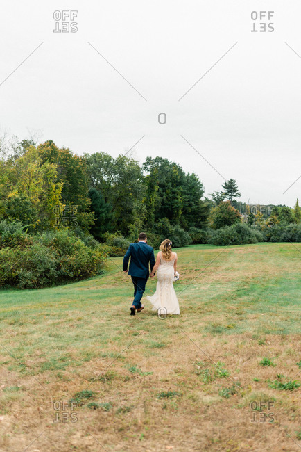 A bride and groom running off into the distance