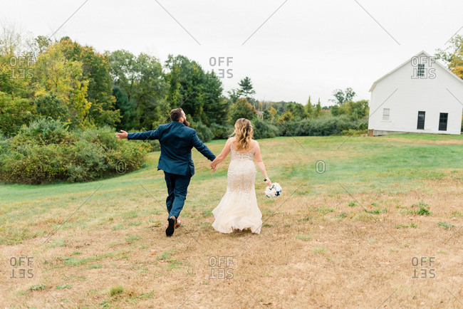 A bride and groom running together