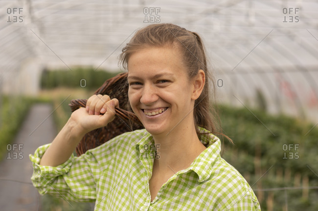 Young woman working as vegetable grower or farmer in a greenhouse