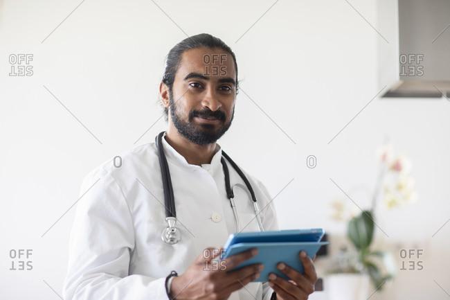 Young male doctor with white coat looking to a report