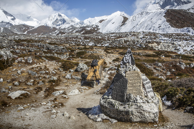 A porter carries goods past prayer stones in Nepal's Khumbu Valley.