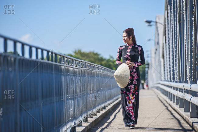Beautiful woman walking over Truong Tien Bridge in Hue / Vietnam