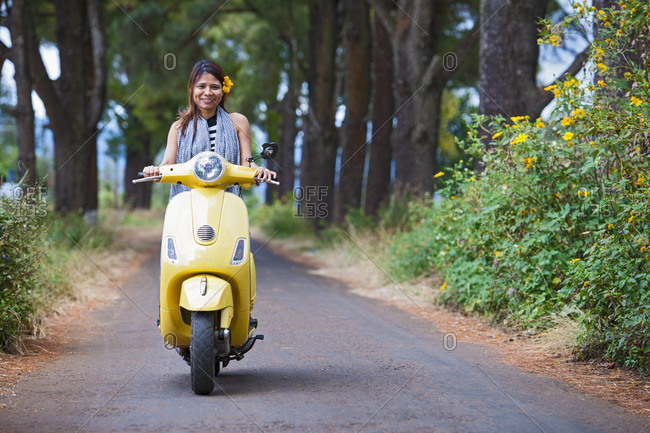 Vietnamese woman with yellow scooter in rural area in Vietnam