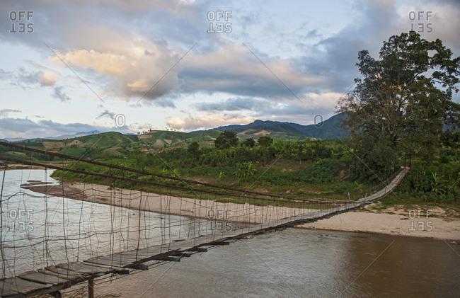 Sketchy suspension footbridge in rural area of Vietnam