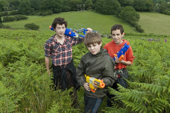 Three teenage boys playing with their toy guns