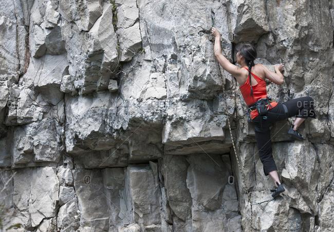 Woman climbing limestone rock face in Swanage / UK