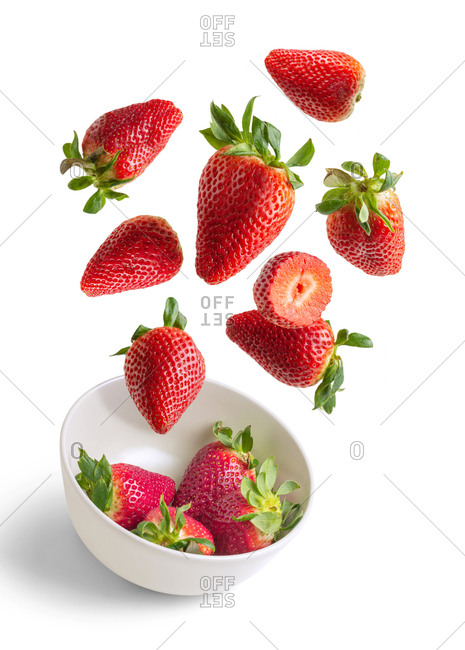 Strawberries flying in white bowl isolated from the background