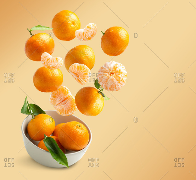 Tangerines flying isolated from orange background with copy space