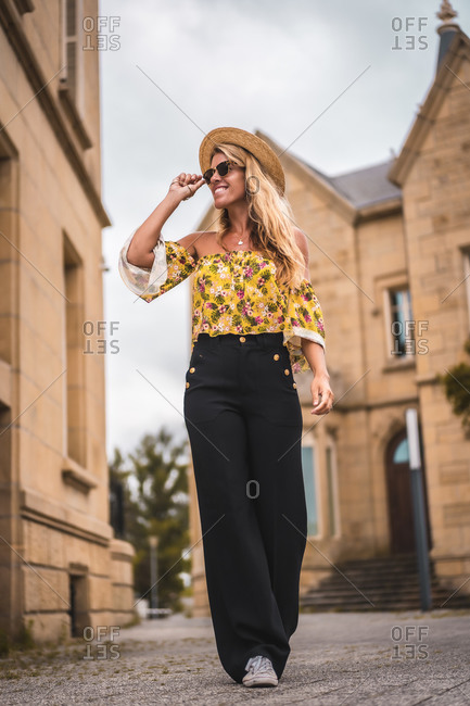 A smiling blonde putting on her sunglasses strolling