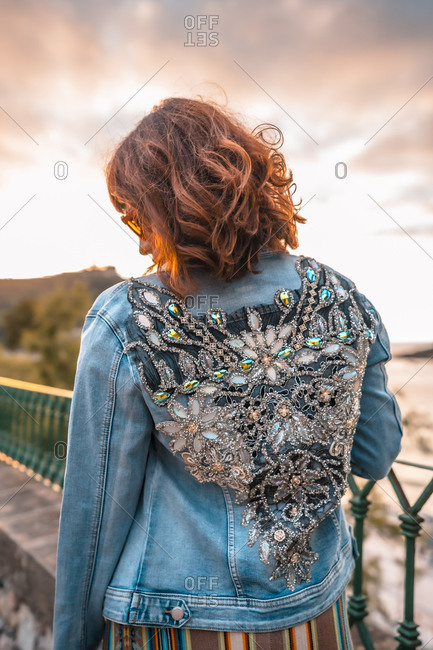 A young woman in a jacket with a beautiful print on the back
