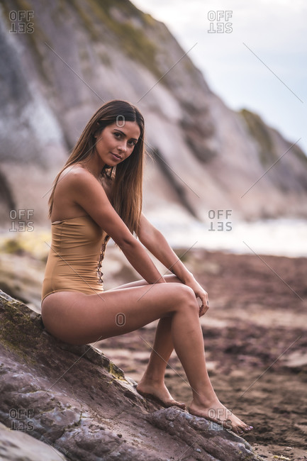 A young woman in a yellow swimsuit sitting on some sea-supported rocks