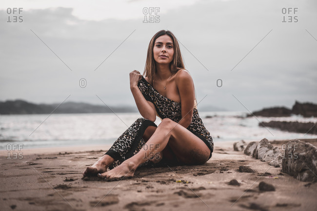 Pretty brunette in a leopard pareo sitting on the sand by the sea