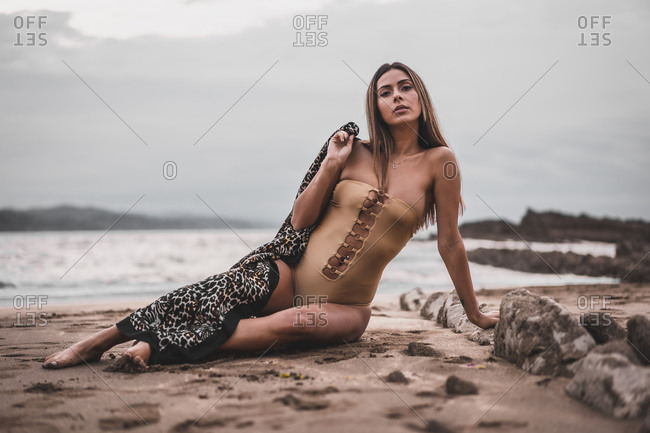 Young girl with dark pareo and swimsuit sitting on the sand by the sea