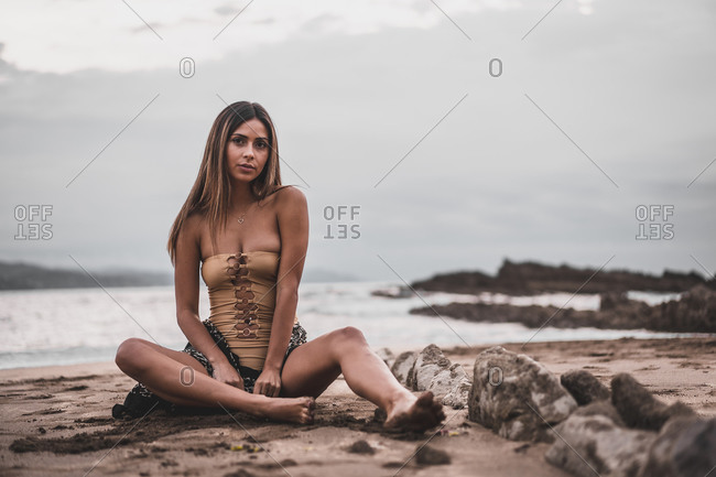 Young girl with pareo and swimsuit sitting on the sand by the sea