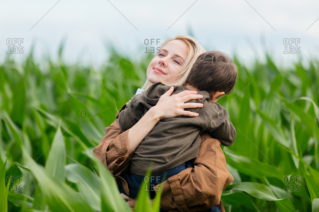 Blonde mother in cloak with a child boy in cornfield in summertime
