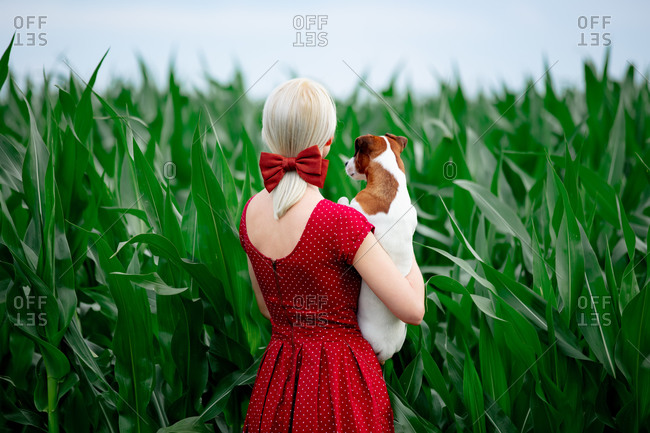 Blonde lady in beautiful red dress with dog in cornfield