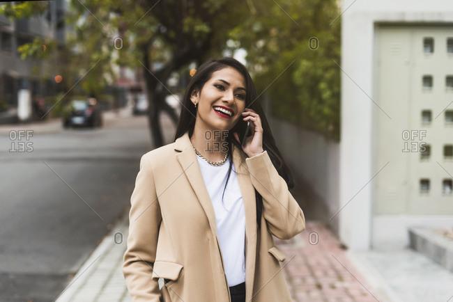 Beautiful Hispanic woman talking on the phone in the street