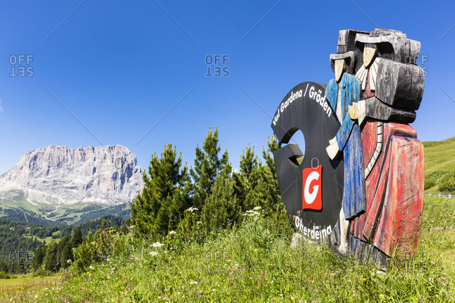 July 20, 2018: Marketing sign of the Groedner Valley on an alpine summer meadow in front of Mount Langkofel (3181m), Groedner Pass, Alto Adige, Tentino, South Tyrol, Italy