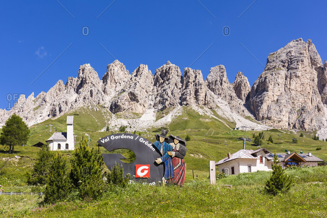 July 20, 2018: Marketing sign of the Groedner Valley on an alpine summer meadow in front of the Puez-Geisler Group, Groedner Pass, Alto Adige, Tentino, South Tyrol, Italy
