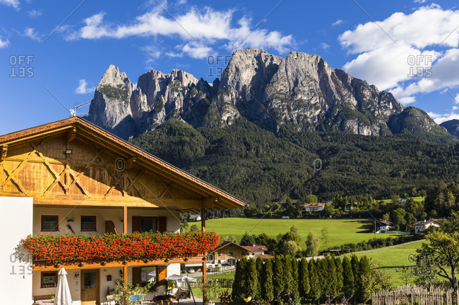 October 3, 2018: Tyical chalet with geranium flower boxes in front of Mount Schlern, Voels am Schlern, UNESCO World Heritage Site, Dolomites, Alps, Alto Adige, Tentino, South Tyrol, Italy