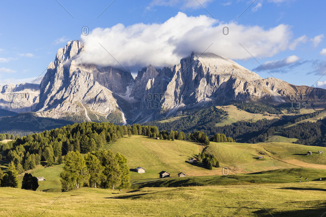 Pastureland and huts in front of Langkofel (3181m) and Plattkofel (2969m) on Seiser Alm, Alpe di Siusi, UNESCO World Heritage Site, Dolomites, Alps, Alto Adige, Tentino, South Tyrol, Italy