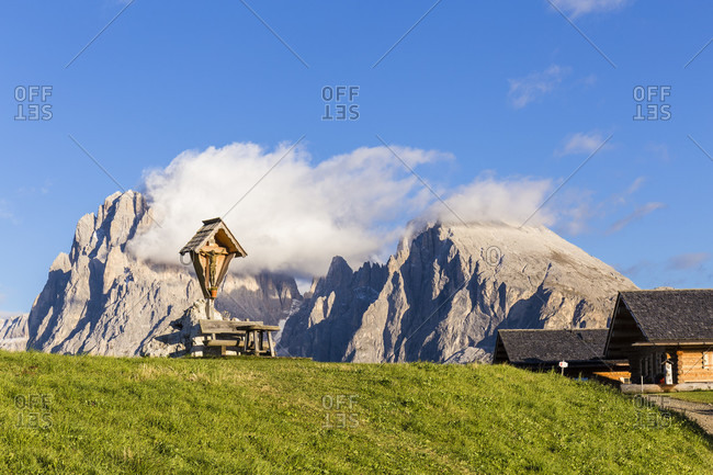 Wooden cross and bench in front of Langkofel (3181m) and Plattkofel (2969m), Seiser Alm, Alpe di Siusi, UNESCO World Heritage Site, Dolomites, Alps, Alto Adige, Tentino, South Tyrol, Italy