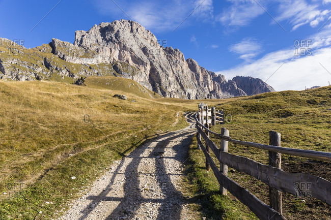 Trail along a fence in front of the Geislerspitzen or Odle Range, Puez-Geisler Nature Park, UNESCO World Heritage Site, Dolomites, Alps, Alto Adige, Tentino, South Tyrol, Italy