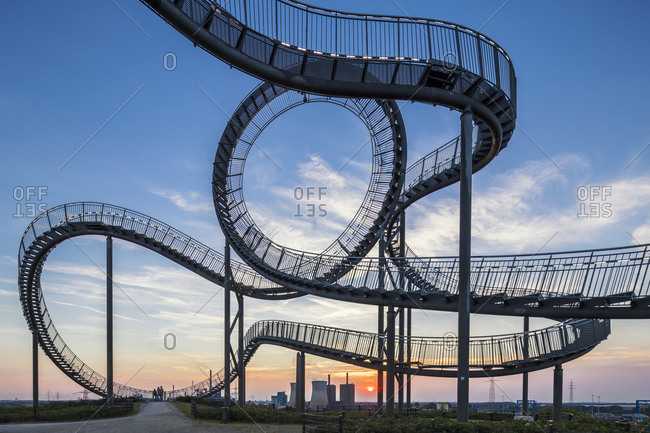August 31, 2016: Power plant with part of the Tiger and Turtle, a pedestrian roller coaster sculpture on Magic Mountain at sunset, Duisburg, Ruhr area, Northrhine Westfalia, Germany