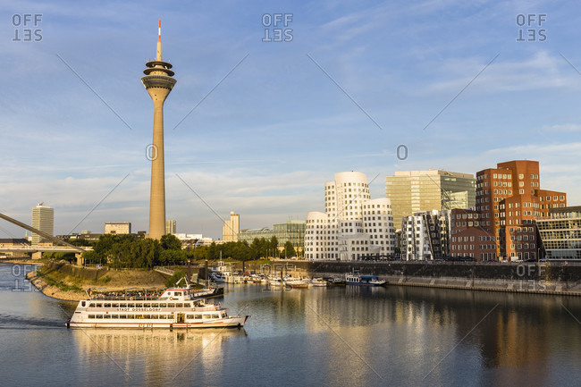 September 3, 2018: Tourist vessel Duesseldorf in front of Rheinturm Tower and Gehry office buildings of Neuer Zollhof at sunset, Media Harbor, Duesseldorf, Northrhine Westfalia, Germany