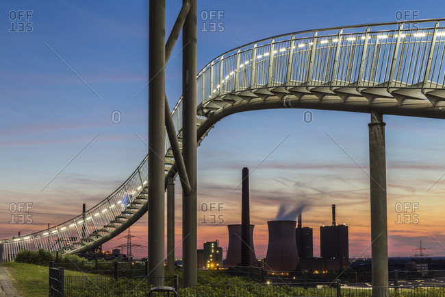 September 6, 2016: Power plant with part of the illuminated Tiger and Turtle, a pedestrian roller coaster sculpture on Magic Mountain at sunset, Duisburg, Ruhr area, Northrhine Westfalia, Germany