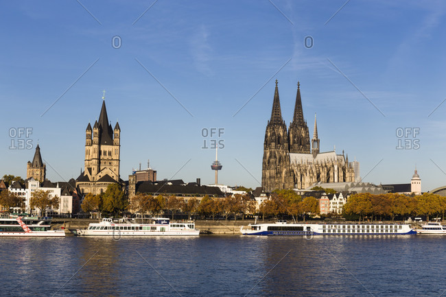 October 31, 2018: Sightseeing vessel on the River Rhine in front of the Cologne Cathedral (Dom) and Gross Sankt Martin Church, autumn, Cologne, Northrhine Westfalia, Germany