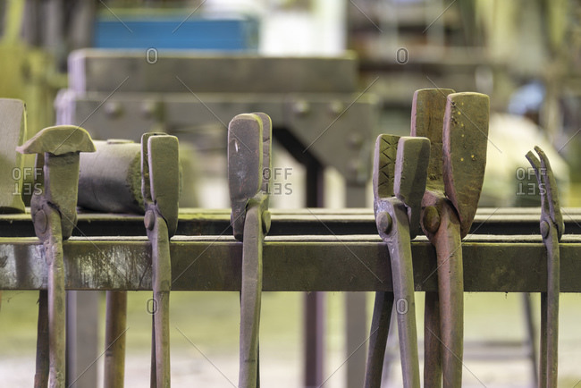 Forging tongs organized on metal stand