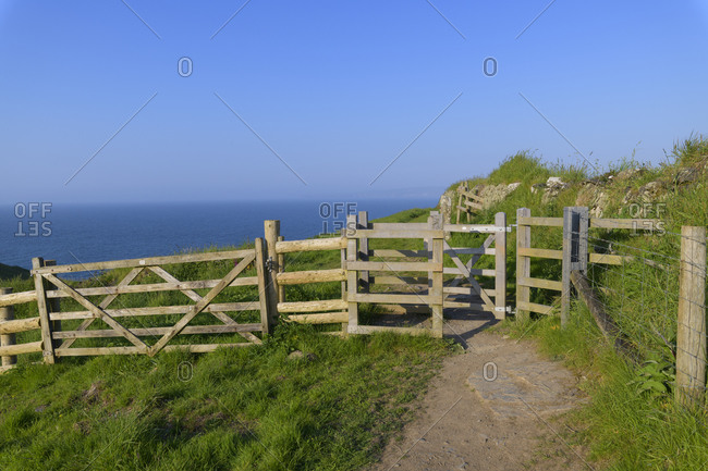 Rocky shore with footpath and gate in spring, The Rumps, Pentireglaze, Wadebridge, Cornwall, South West England, England, United Kingdom, Europe