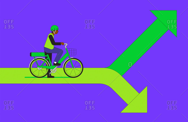 Cyclist on electric bike facing choice of green arrows