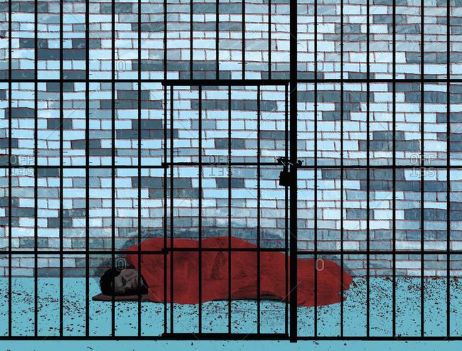 Homeless person asleep on floor behind bars