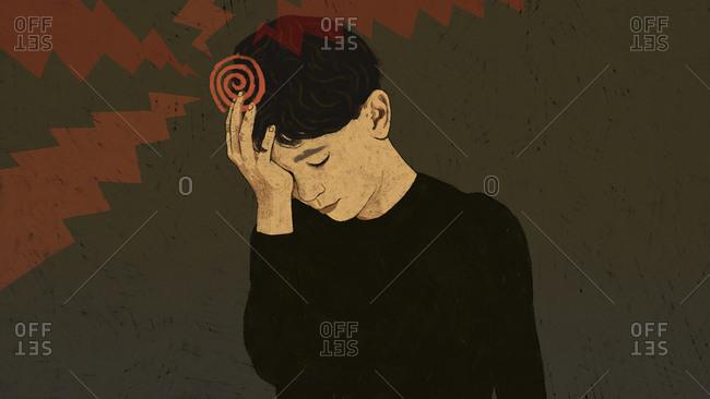 Boy with headache holding hand to head