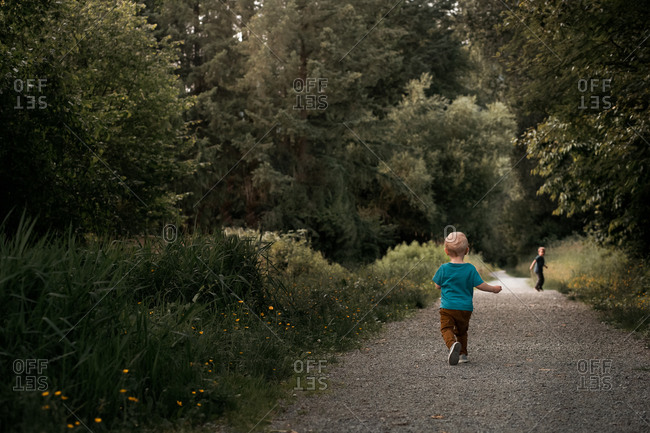 Toddler boy chasing his brother on a gravel path