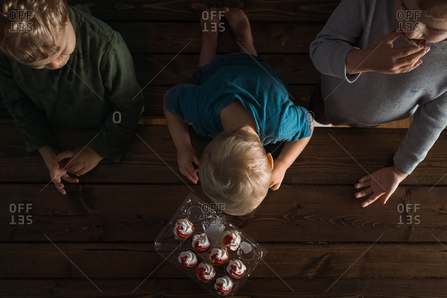 Overhead view of three little boys eating store-bought cupcakes on wooden table